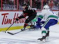Ottawa Senators left wing Brady Tkachuk (7) flattens Vancouver Canucks center Brandon Sutter (20) and controls the puck against center Zack MacEwen (71) during first period NHL action at the Canadian Tire Centre, Apr. 28, 2021.