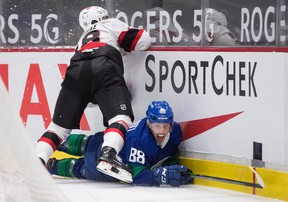 Ottawa Senators' Tim Stuetzle misses the check on Vancouver Canucks' Nate Schmidt and crashes into the boards on Thursday night.