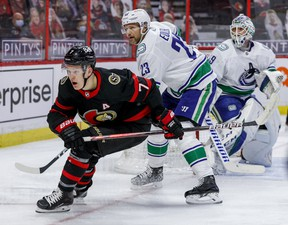 Ottawa Senators winger Brady Tkachuk (7) and Vancouver Canucks defenceman Alexander Edler  in front of goaltender Braden Holtby on Monday night at the Canadian Tire Centre.