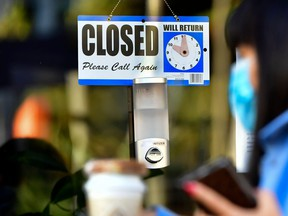 In this file photo a pedestrian wearing her facemask and holding a cup of coffee walks past a closed sign hanging on the door of a small business.