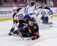 Senators forward Ryan Dzingel (10) is hauled down by Winnipeg Jets center Mason Appleton  during the first period on Monday night at the Canadian Tire Centre.