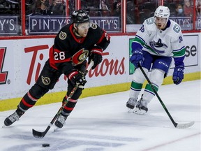Ottawa Senators right wing Connor Brown eludes the check of Vancouver Canucks defenceman Nate Schmidt.