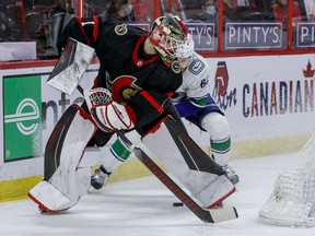 Ottawa Senators goaltender Marcus Hogberg loses a puck battle behind his net with Vancouver Canucks centre Tyler Motte, April 28, 2021.