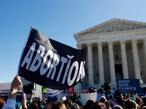 A demonstrator holds up an abortion flag outside of the U.S. Supreme Court as justices hear a major abortion case on the legality of a Republican-backed Louisiana law that imposes restrictions on abortion doctors, on Capitol Hill in Washington, D.C., March 4, 2020.