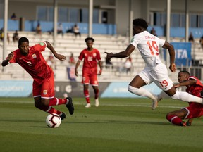 Alphonso Davies of Canada (No. 19) challenges Cameron Gray (No. 2) of the Cayman Islands in a 2022 FIFA World Cup qualifying game at the IMG Academy in Bradenton, Fla., on Mar. 29. 2021.