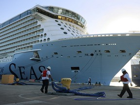 Dock workers use ropes to tie the Royal Caribbean's Odyssey of The Seas to its berthing spot at Port Everglades on June 10, 2021 in Fort Lauderdale, Florida.
