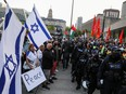 Police officers stand in line to separate protesters supporting Palestine from a small group of Israel supporters in front of city hall in Toronto May 15, 2021.