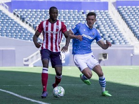 FC Edmonton defender Amer Didic challenges Atletico Ottawa forward Malcolm Shaw for the ball in a Canadian Premier League match at Investors Group Field in Winnipeg, Man., on June 26, 2021.
