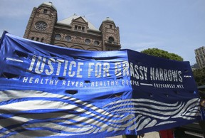 Banner demanding justice for northern Ontario First Nations community Grassy Narrows at Queen's Park in June 2016