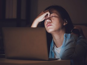 A woman working late at night, suffering burnout.