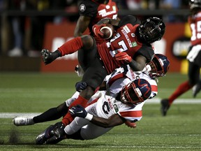 Ottawa Redblacks wide receiver DeVonte Dedmon (17) is tackled by Montreal Alouettes defensive back Adarius Pickett (6) and defensive back Rodney Randle Jr. (32) during first half CFL football action in Ottawa on Friday, Sept. 3, 2021.