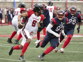 Ottawa Redblacks quarterback Caleb Evans runs with the ball during second half CFL football action against the Montreal Alouettes in Montreal, Monday, October 11, 2021.