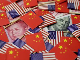 A U.S. dollar banknote featuring American founding father Benjamin Franklin and a China's yuan banknote featuring late Chinese chairman Mao Zedong are seen among U.S. and Chinese flags.