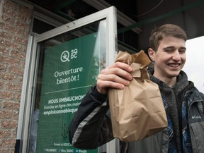 In this file photo taken on October 17, 2018, a young man holds a bag of marijuana he bought in a cannabis store in Quebec City.