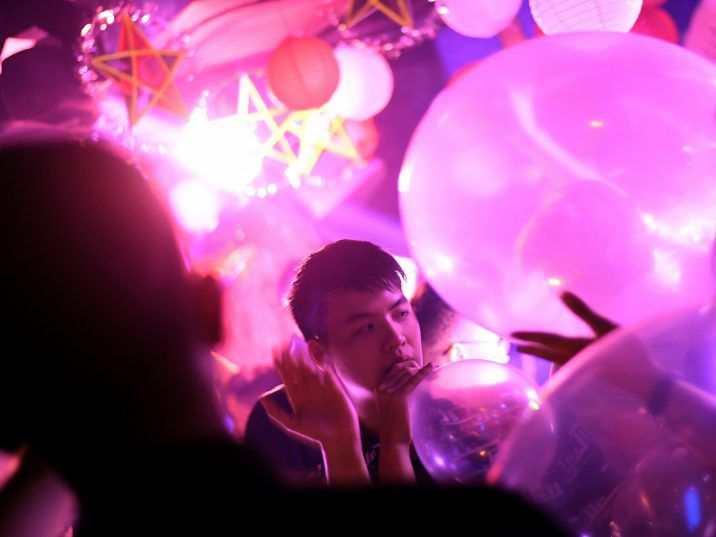"""FILE: In this picture taken on Sept. 22, 2018, a Vietnamese youth inhales a """"funky balloons"""" filled with laughing gas, at a nightclub in Hanoi."""