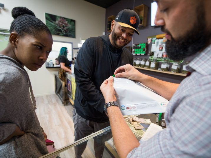 Budtender Danny Buelna (R) shows customers Mariah Roy (L) and Edward Ochoa (C) how to use the required child-proof bag for their purchases at the Green Pearl Organics dispensary on the first day of legal recreational marijuana sales in California, January 1, 2018 in California.