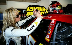 Miss Sprint Cup, Kristen Beat, snaps a picture of Clint Bowyer's helmet Friday during preparations for Sunday's Daytona 500. Getty Images photo.