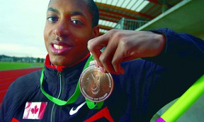 Langley Secondary's Braedon Dolfo shows the bronze medal he won when he set the Canadian record in the high jump at the 2011 Paralympic World Championships in New Zealand. (Photo -- Troy Landreville, The Langley Advance)