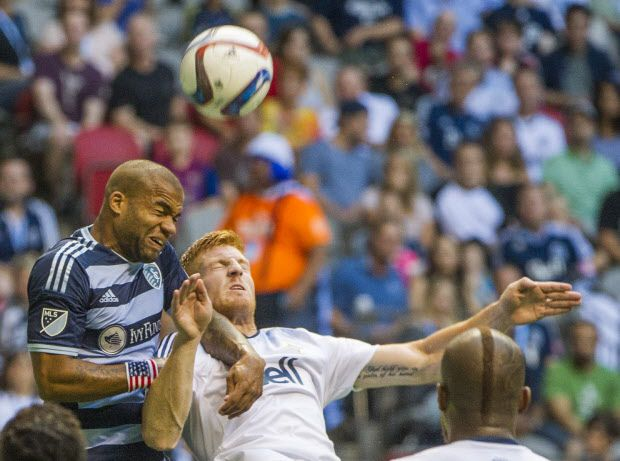 VANCOUVER, BC: July 12, 2015 -- Whitecaps Tim Parker, right battles for the ball with Sporting KC Kevin Ellis, left during the first half of a regular-season MLS match at BC Place Stadium in Vancouver, B.C. Sunday July 12, 2015.   (photo by Ric Ernst / PNG)  (Story by sports)  TRAX #: 00037667A & 00037667B [PNG Merlin Archive]