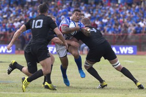 Samoa's Tusiata Pisi, center, tries to run through a defense of New Zealand All Blacks during their rugby union match at Apia Park in Apia, Samoa, Wednesday, July 8, 2015. New Zealand won the match 25-16 in the All Blacks' first-ever test match in the Pacific Island nation. (Dean Purcell/New Zealand Herald via AP)