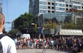 Busker Daniel Zindler is pictured here in a screen grab from a YouTube video taken in downtown Vancouver as he regains his balance after a kid interfered with his stunt.