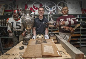 Curator Jason Beck with Lois Fisher's scrapbook from UBC women's 1930 basketball team, a 1970 Vancouver Canucks puck that was dropped for their first opening face-off, the Buchanan Cup trophy (for rowing) and Whitecaps' 1979 NASL trophy, mannequins of B.C. Lions player Willie Fleming (far left) and Vancouver Millionaires' Cyclone Taylor (far right).
