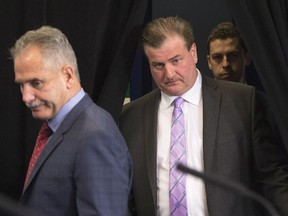 Vancouver Canucks general manager Jim Benning, right, and head coach Willie Desjardins arrive for a news conference in Vancouver, B.C., Tuesday, April 12, 2016. THE CANADIAN PRESS/Jonathan Hayward