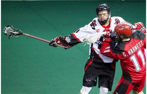 The Vancouver Stealth's Logan Schuss works against Greg Harnett, right, of the Calgary Roughnecks.