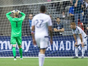 Vancouver Whitecaps' goalkeeper David Ousted, from left, Blas Perez and Tim Parker look on after Toronto FC's Will Johnson, not seen, scored in the final moments during second half Canadian Championship final soccer action to win the Voyageurs Cup on aggregate in Vancouver, B.C., on Wednesday June 29, 2016.