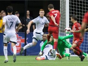 Toronto FC's Will Johnson (7) scores a goal in the final moments against Vancouver Whitecaps goalkeeper David Ousted, bottom, during second half Canadian Championship final soccer action to win the Voyageurs Cup on aggregate in Vancouver, B.C., on Wednesday June 29, 2016.