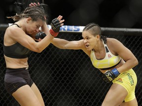 Amanda Nunes, right, hits Miesha Tate during their women's bantamweight championship mixed martial-arts bout at UFC 200, Saturday in Las Vegas. — The Associated Press