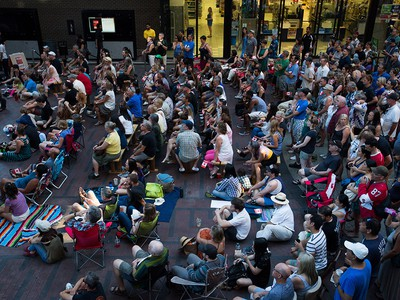 People gather during a viewing party for the final stop in Kingston, Ont., of a 10-city national concert tour by The Tragically Hip, in Vancouver, B.C., on Saturday August 20, 2016. Lead singer Gord Downie announced earlier this year that he was diagnosed with an incurable form of brain cancer. THE CANADIAN PRESS/Darryl Dyck ORG XMIT: VCRD112