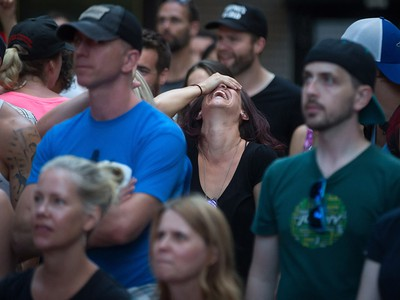 A woman, centre, reacts during a viewing party for the final stop in Kingston, Ont., of a 10-city national concert tour by The Tragically Hip, in Vancouver, B.C., on Saturday August 20, 2016. Lead singer Gord Downie announced earlier this year that he was diagnosed with an incurable form of brain cancer. THE CANADIAN PRESS/Darryl Dyck ORG XMIT: VCRD126