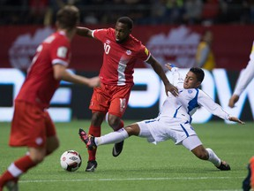 Canada's Junior Hoilett, centre, fights off a challenge from El Salvador's Oscar Ceren, right, to get the ball to teammate Nik Ledgerwood, front left, who sored on the play during second half FIFA World Cup qualifying soccer action in Vancouver, B.C., on Tuesday September 6, 2016.