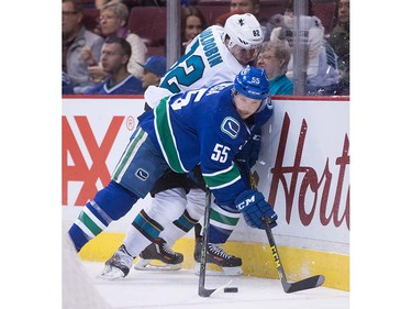 Vancouver Canucks' Alex Biega, front, and San Jose Sharks' Nikolay Goldobin, of Russia, battle for the puck during the first period of a pre-season NHL hockey game in Vancouver, B.C., on Sunday October 2, 2016.