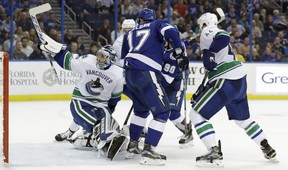 Vancouver Canucks goalie Ryan Miller (30) bats the puck out of the air after making a save on a shot by Tampa Bay Lightning left wing Alex Killorn.