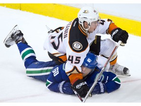 Anaheim Ducks' Sami Vatanen, top, of Finland, falls on Vancouver Canucks' Markus Granlund, of Finland, after taking him down on a breakaway during the second period of an NHL hockey game in Vancouver, B.C., on Thursday December 1, 2016.