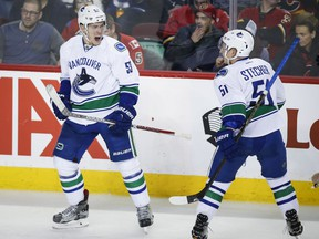 Canucks centre Bo Horvat, left, celebrates his goal with teammate Troy Stecher during Vancouver's 3-1 loss in in Calgary on Saturday.
