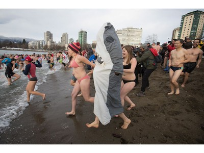 A man dressed in a shark costume and other participants run into the waters of English Bay during the Polar Bear Swim, in Vancouver, B.C., on Sunday, January 1, 2017. The event, hosted by the Vancouver Polar Bear Swim Club, was first held on new year's day in 1920.