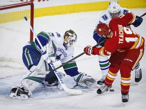 Vancouver Canucks goalie Jacob Markstrom, left, of Sweden, grabs for the puck as Calgary Flames' Matthew Tkachuk looks on during third period NHL hockey action in Calgary, Saturday, Jan. 7, 2017.