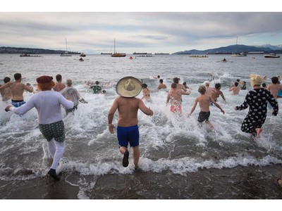 Participants run into the frigid waters of English Bay during the Polar Bear Swim in Vancouver, B.C., on Sunday, January 1, 2017. The event, hosted by the Vancouver Polar Bear Swim Club, was first held on new year's day in 1920.