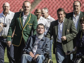 Rugby World Cup winning team captain Francois Pienaar (lest) assisted his former teammate Joost van der Westhuizen during a re-enactement of the team photo from the 1995 Rugby World cup victory on June 24, 2015 at Ellis Park in Johannesburg.