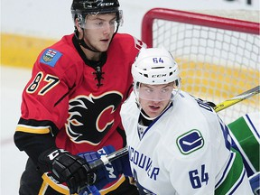 Vancouver Canucks prospect Tate Olson, right, patrols the crease in front of Calgary Flames Mathieu Sevigny during NHL Young Stars Classic action at the South Okanagan Events Centre in Penticton on Sept. 19, 2016.