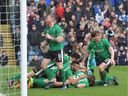 Lincoln City's English defender Sean Raggett, centre, celebrates with teammates after scoring  during the English FA Cup fifth round football match between Lincoln City and Burnley at the Sincil Bank stadium in Lincoln, eastern England, in February.