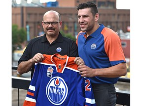 Edmonton Oilers general manager Peter Chiarelli poses with free agent forward Milan Lucic last summer.