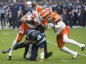 Toronto Argonauts quarterback Ricky Ray, centre, is sacked by BC Lions' DeQuin Evans, left, and Bryant Turner Jr. during first half CFL football action in Toronto on Friday.