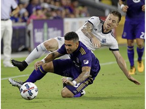 Dom Dwyer of the Orlando City FC Lions, front, gets tangled up with Jordan Harvey of the Vancouver Whitecaps while going for the ball during Saturday's Major League match in Florida. The Whitecaps won 2-1.