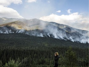A woman stops on the side of the highway to watch a forest fire burn near Revelstoke on Aug. 19.
