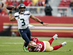 Seattle Seahawks quarterback Russell Wilson (3) throws while being tackled by San Francisco 49ers defensive tackle DeForest Buckner (99) during the first half of an NFL football game Sunday, Nov. 26, 2017, in Santa Clara, Calif.
