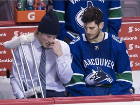 Vancouver Canucks right wing Brock Boeser is seen with crutches as he speaks to Vancouver Canucks center Nic Dowd following a loss to the Calgary Flames in Vancouver, Sunday. Boeser took a shot of his left foot early in the second period of Sunday's game against the Calgary Flames and did not return.